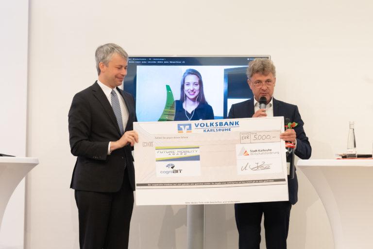 """Steffen Bilger (l.) und Dr. Frank Mentrup überreichen auf der hybriden Regionalkonferenz Mobilitätswende den Preis des """"Future Mobility Award 2021"""" an Dr. Isabelle Garzorz vom Start-up cogniBIT. (Quelle: TechnologieRegion Karlsruhe GmbH)"""